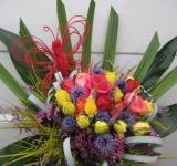 Kytice z růží, bělotrnu a dalších trvalek, doplněná palmovými listy
